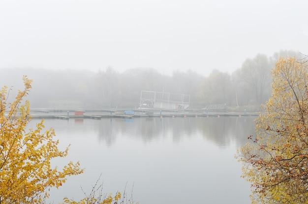 Rosyjski upadek. jesienne drzewa odbijają się w jeziorze. piękny, mglisty, jesienny poranek nad jeziorem