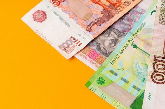 Rosyjskich rubli banknoty i ukraiński hrywien na żółtym tle z bliska