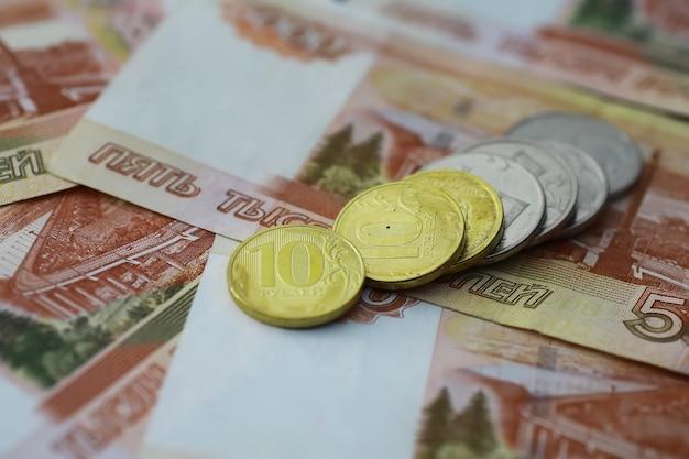 """Rosyjskie banknoty i monety """"ruble"""". banknot z napisem """"pięć tysięcy rubli"""" oraz monety 5 i 10 rubli. tło z pieniędzy."""