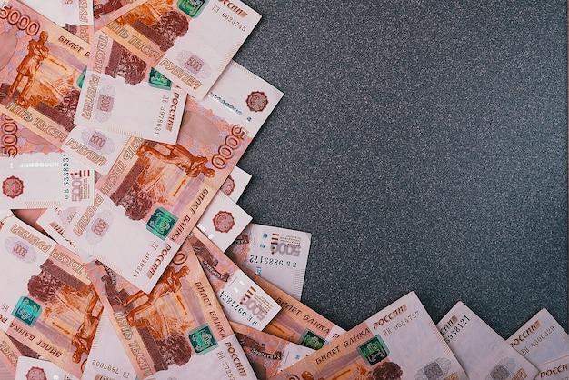 Rosyjskie banknoty pieniężne o wartości pięciu tysięcy rubli, rozrzucone na szarym tle