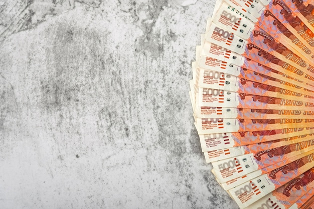 Rosyjskie banknoty pieniężne o wartości pięciu tysięcy rubli, tło, banknoty są ułożone w wachlarz na szarym tle.