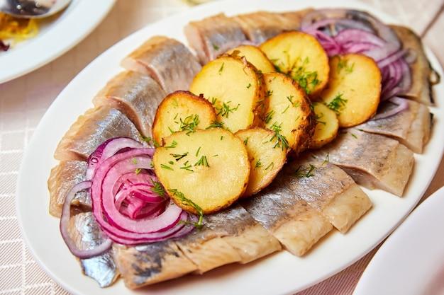 Rosyjskie danie noworoczne. śledź z ziemniakami i słodką cebulą