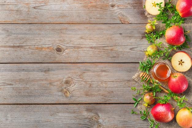 Rosz haszana, koncepcja wakacje żydowskiego nowego roku z tradycyjnymi symbolami, jabłka, miód, granat na drewnianym stole w stylu rustykalnym. kopiuj przestrzeń, płaskie tło świecące
