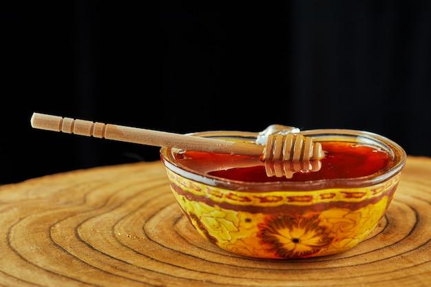 Rosz haszana - koncepcja żydowskiego święta nowego roku. miska z miodem i drewnianym kijem na tle drewnianych.