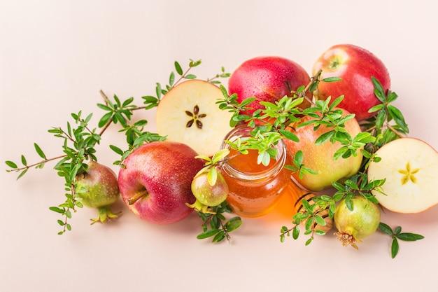 Rosz haszana, żydowska koncepcja święta nowego roku z tradycyjnymi symbolami, jabłkami, miodem, granatem na pastelowym różowym, morelowym stole