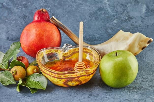 Rosz haszana - żydowska koncepcja wakacje nowy rok. miska w kształcie jabłka z miodem, granatem, szofarem to tradycyjne symbole święta