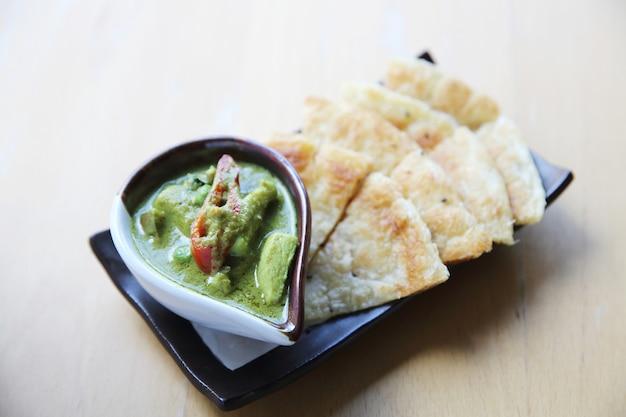 Roti z zielonym curry na drewnianym tle