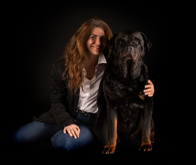 Rottweiler czystej krwi i kobieta na czarnym tle