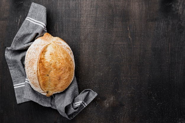 Round chleb na płótnie z kopii przestrzeni drewnianym tłem