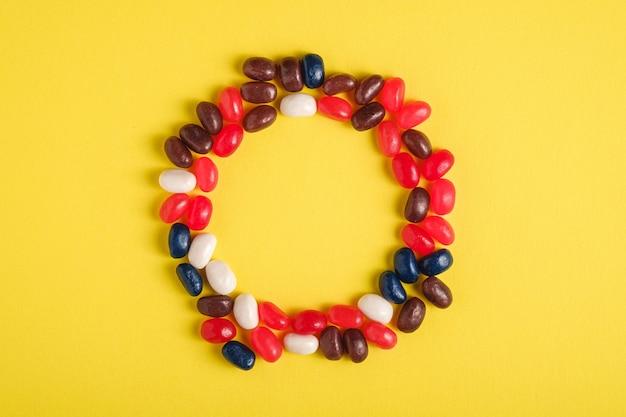 Round rama soczyste słodkie owocowe kolorowe galaretowe fasole na jaskrawej kolor żółty powierzchni, odgórnego widoku kopii przestrzeń