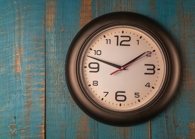Round ścienny zegar przeciw staremu drewnianemu błękita stołowi.