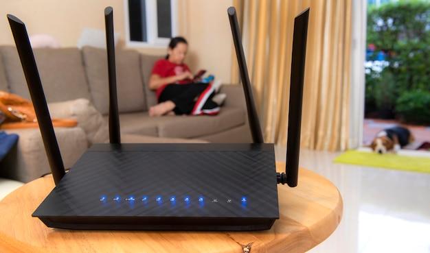 Router bezprzewodowy i kobieta za pomocą telefonu w salonie w domu