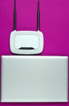 Router wi-fi, laptop, mysz komputerowa na różowym tle