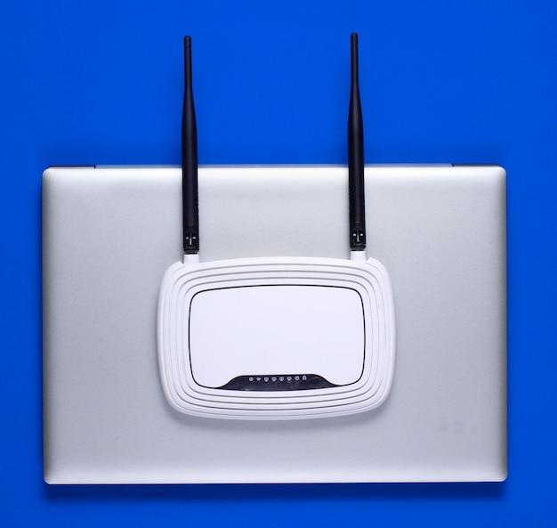 Router wi-fi, laptop na niebieskim tle