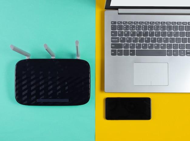 Router wi-fi, smartfon, laptop na kolorowej powierzchni. nowoczesne gadżety.