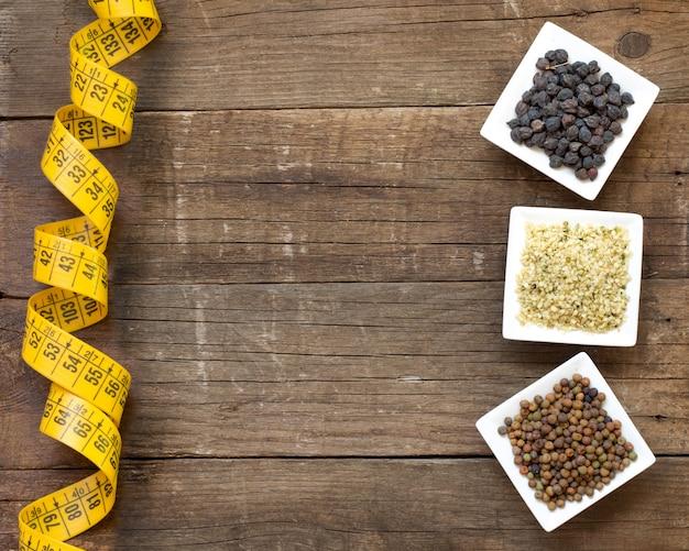 Roveja, nasiona konopi i czarny ciecierzyca z miara zwijana na drewnianym blacie widok z miejsca kopiowania