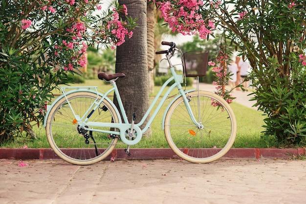 Rower damski vintage w pobliżu zielonych krzewów z kwiatami
