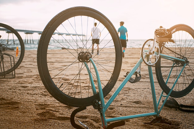 Rower do góry nogami na piasku młodzi ludzie spędzający wolny czas na plaży skopiuj miejsce