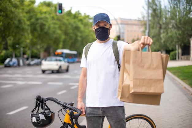 Rower dostawczy z maską koronawirusa z plecakiem i torbami