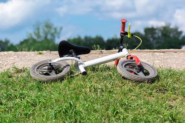 Rower dziecięcy leży na trawie.