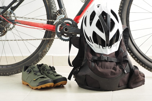 Rower górski, buty welurowe, plecak i biały kask w domu.
