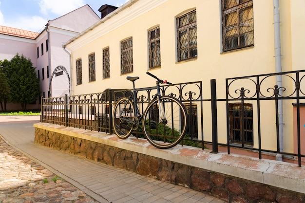 Rower jest zaparkowany w mieście pod płotem.