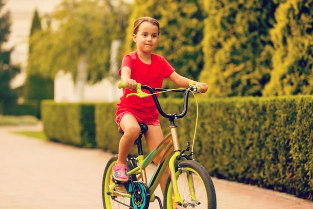 Rower jeździecki dla dzieci. dzieciak na bicyklu w pogodnym parku.