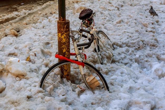 Rower pod śniegiem, parkowanie na ulicy