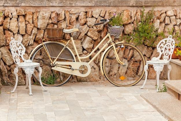 Rower starodawny. vintage rower na zewnątrz z kwiatami, dwa stylowe krzesła przy ścianie z cegły.