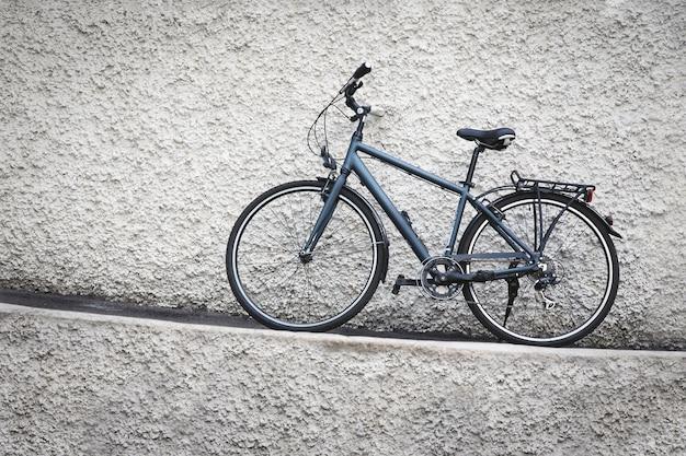 Rower zaparkowany przed grungy kamiennym murem