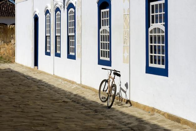 Rower zaparkowany przy białej ścianie z niebieskimi oknami