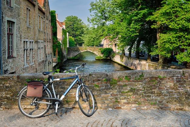 Rowerem na moście w pobliżu kanału i starych domów. bruges brugge, belgia