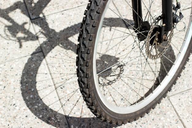 Rowerowa opona przedniego koła i sylwetka cienia na powierzchni miejskich płytek betonowych