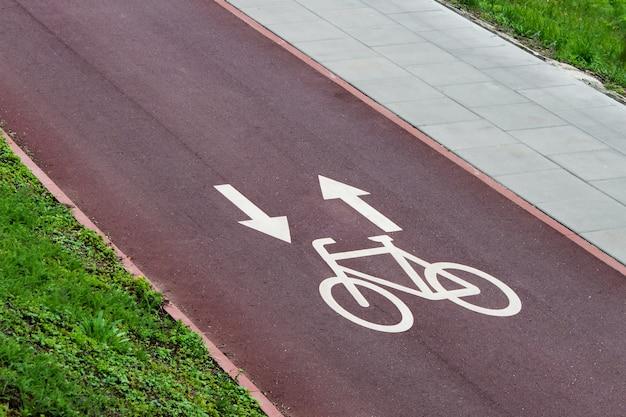 Rowerowe znaki pasa ze strzałkami na czerwonym szlaku rowerowym miasta