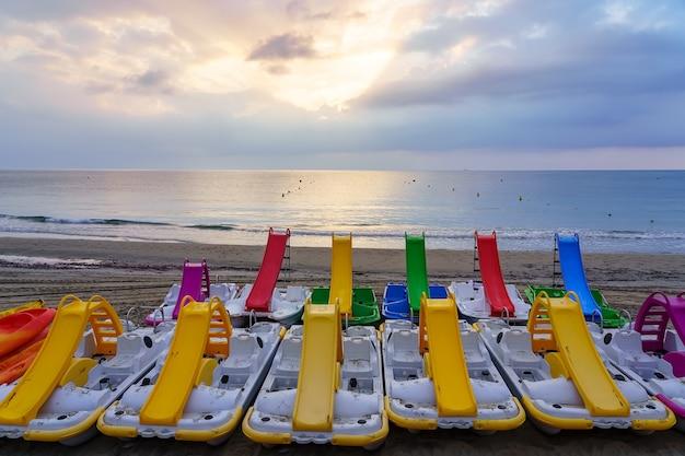 Rowery wodne ze zjeżdżalnią w wielu kolorach na plaży o wschodzie słońca.