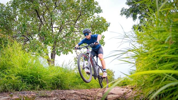 Rowerzyści górscy jeżdżą na mtb, zjazdach na rowerze górskim do granic możliwości. azjata jeździ na mtb, na rowerze górskim w dziczy do ekstremalnych warunków. sport ekstremalny i mtb, koncepcja rowerów górskich.