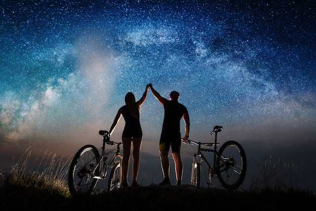 Rowerzyści mężczyźni i kobiety z rowerami górskimi trzymają ręce uniesione do nieba na wzgórzu.
