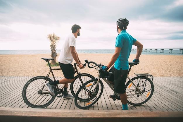 Rowerzyści na chodniku na plaży z widokiem na morze z mostem w tle copyspace sport