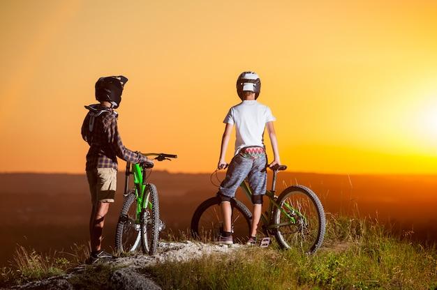 Rowerzyści z rowerami górskimi na wzgórzu wieczorem
