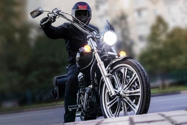 Rowerzysta człowiek na motocyklu wieczorem na ulicy miasta. zbliżenie. nocny motocyklista.
