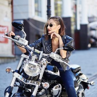 Rowerzysta dziewczyna w skórzanej kurtce na motocyklu