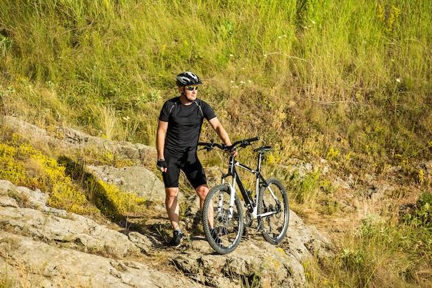 Rowerzysta górski z rowerem na skale. motywacja i inspiracja do przygody.