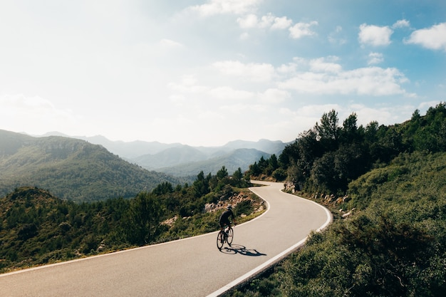 Rowerzysta, jazda na rowerze o zachodzie słońca w górskiej jezdni