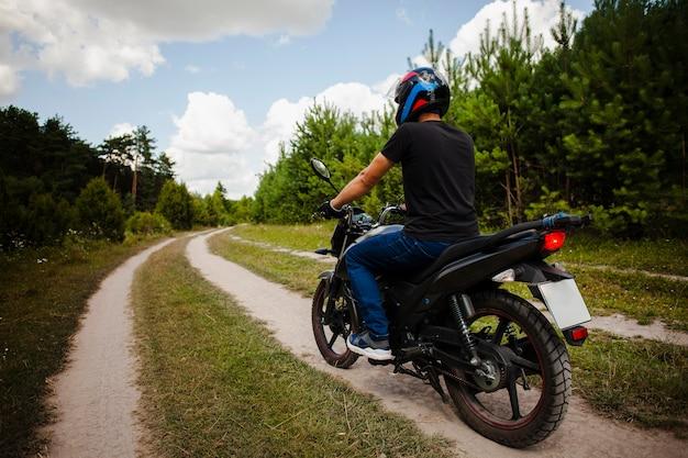Rowerzysta jedzie motocykl na polnej drodze z hełmem