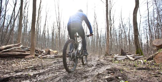 Rowerzysta jedzie na rowerze górskim na szlaku w lesie
