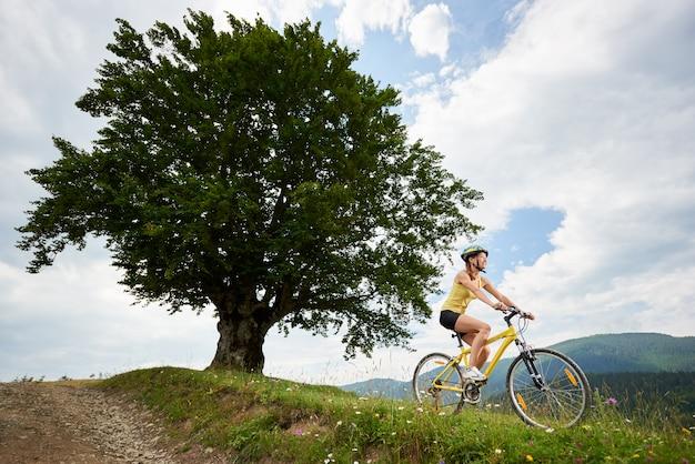 Rowerzysta jedzie na żółtym rowerze górskim