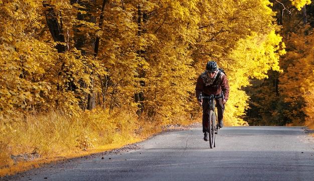 Rowerzysta jeździ drogą na rowerze w jesiennym lesie z żółtymi liśćmi.