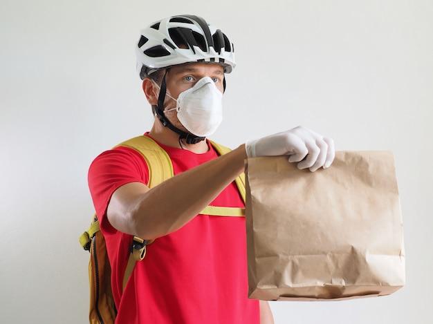 Rowerzysta kurierski dostarcza papierową torbę. usługa dostarczania podczas koronawirusa kwarantanny.