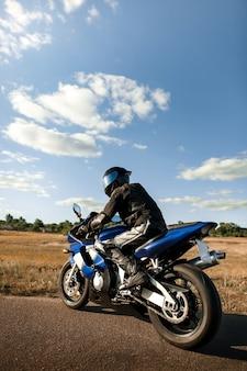 Rowerzysta lub motocyklista w czarnym skórzanym kombinezonie i kasku siedzi na motocyklu sportowym i spogląda w dal.