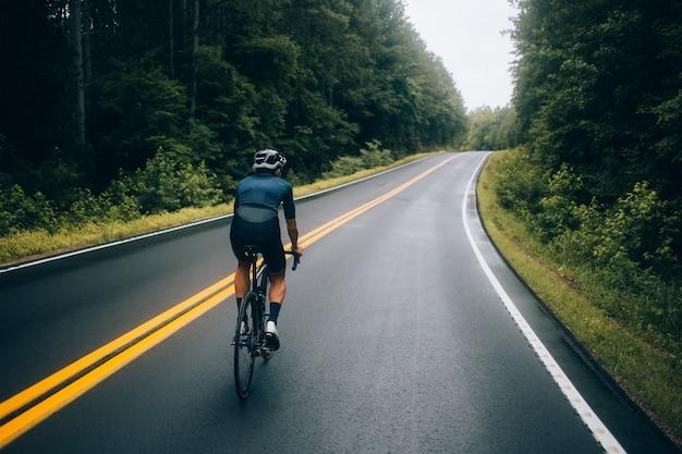 Rowerzysta mężczyzna jedzie na rowerze na drodze